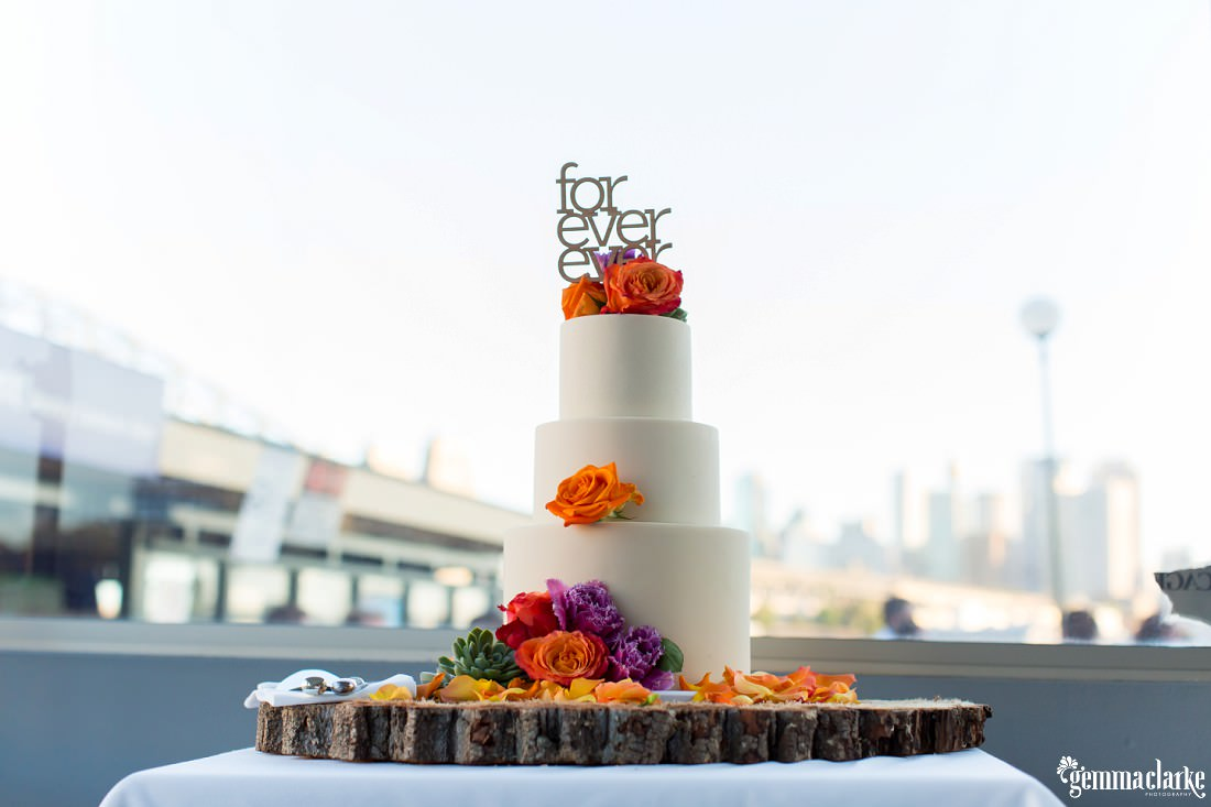 "A three tiered white wedding cake with colourful floral decorations and cake topper that says ""for ever ever"""