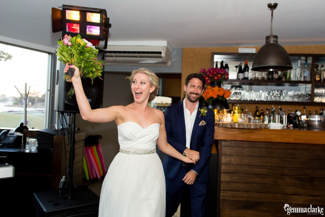 A smiling bride holds her bouquet in the air as her and her smiling groom make an entrance to their wedding reception