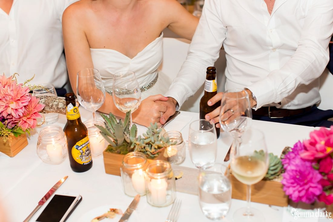 A bride and groom hold hands at their wedding reception