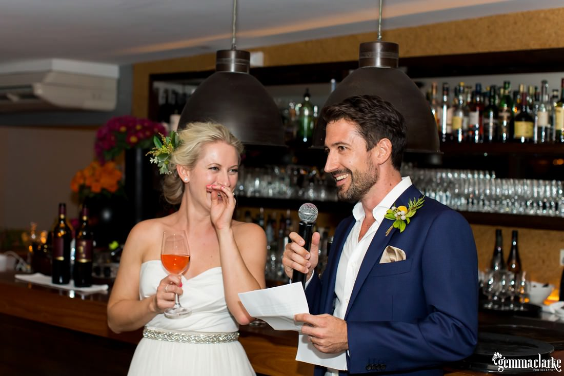 A bride covers her smiling mouth with her hand as her groom makes a speech