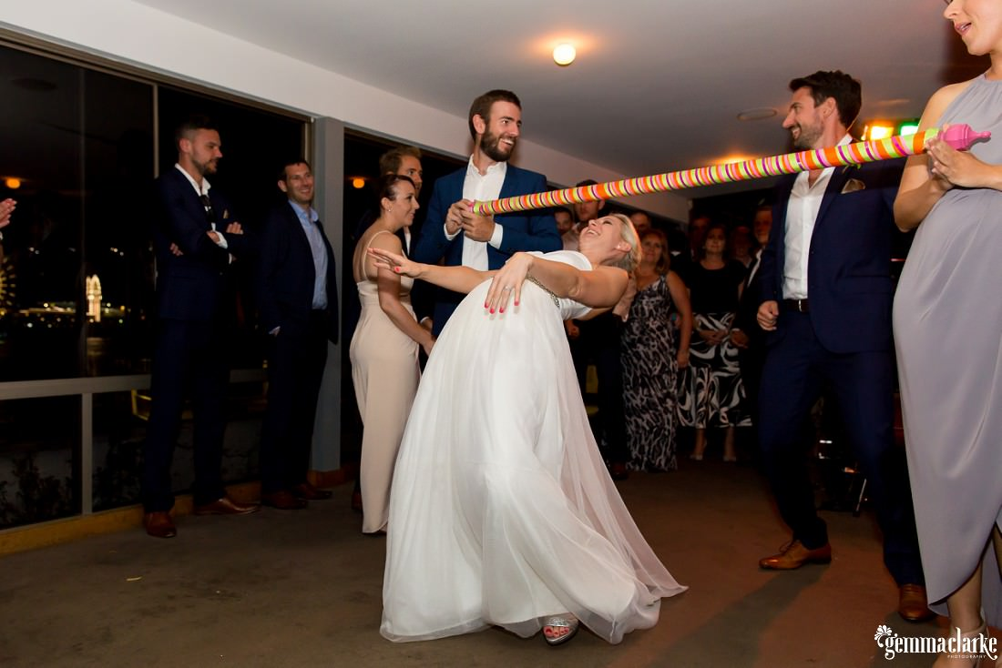 A bride does limbo under a bar being held by a groomsman and a bridesmaid at her wedding reception