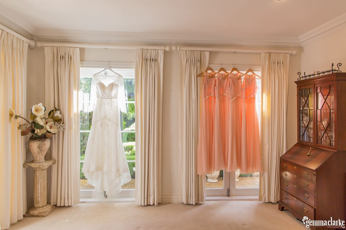 Four peach coloured bridesmaids dresses and a long-sleeved lacy white bridal gown hanging in a living room