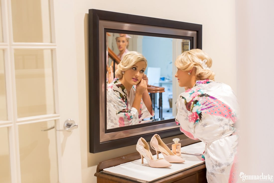 A bride putting on her earrings in front of a mirror