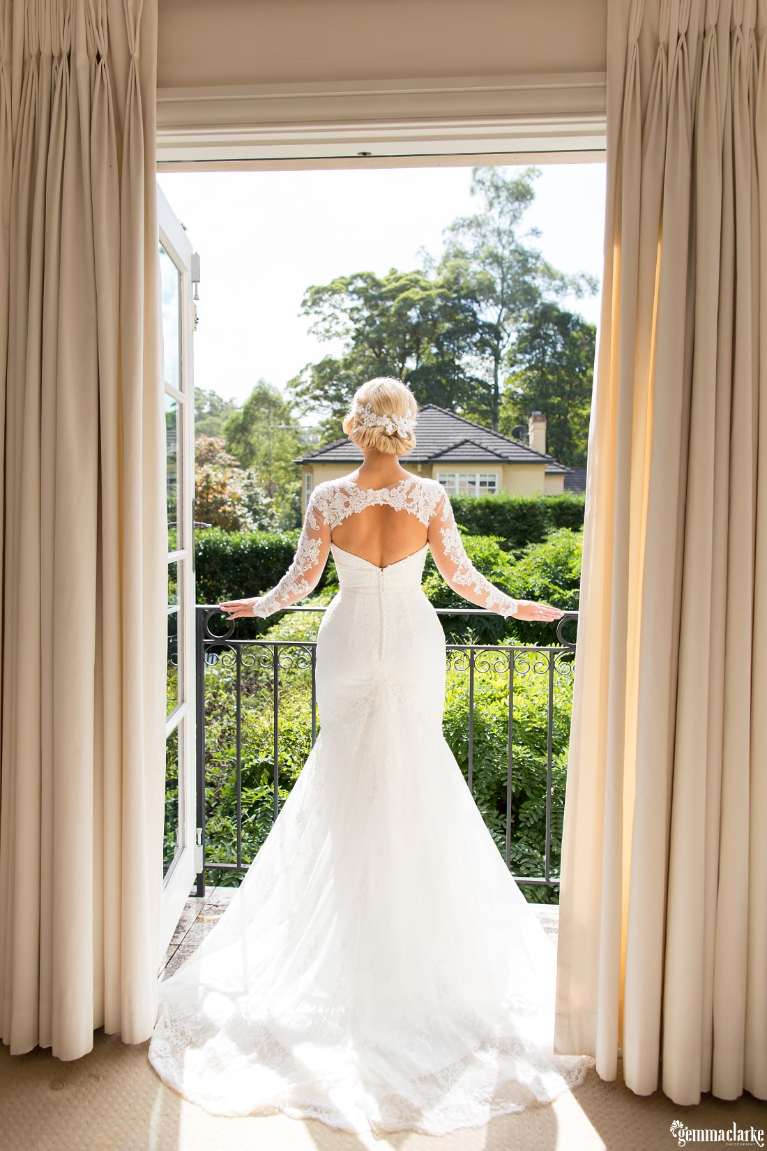 A bride in a lovely lacy wedding dress looking out from a balcony