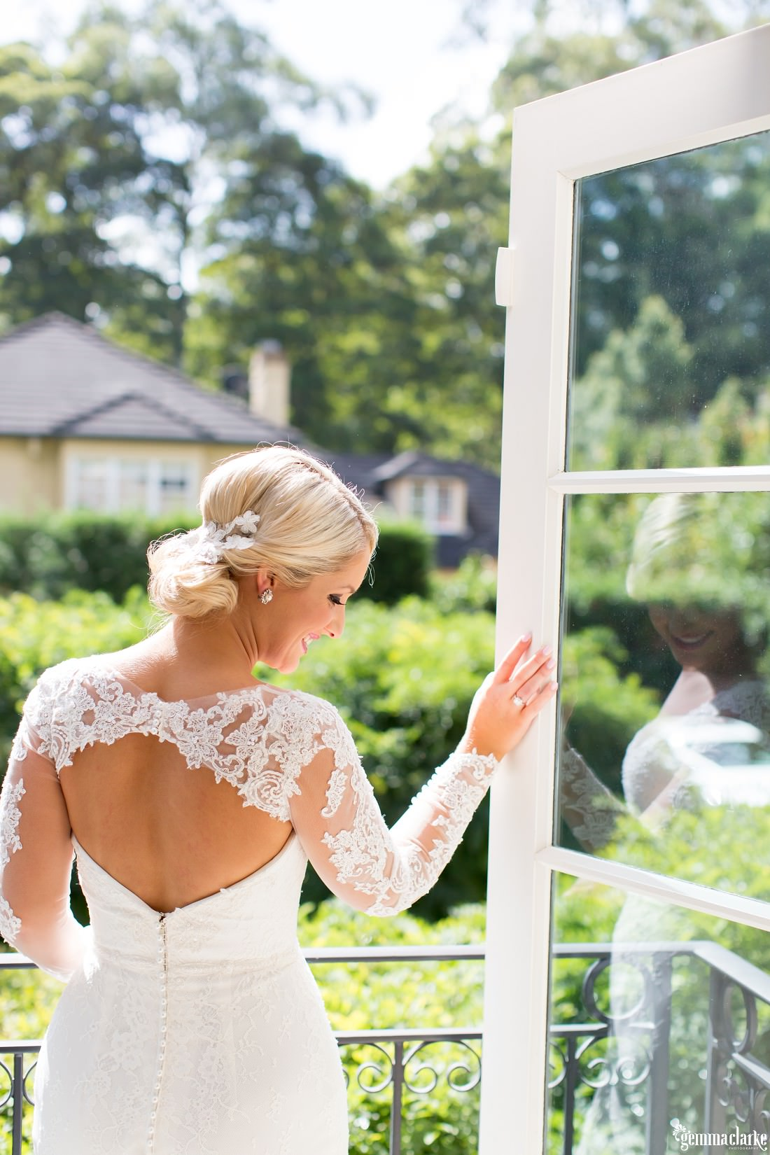 A bride in a lovely lacy wedding dress with her hand on a door looking back over her shoulder