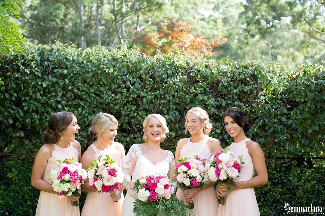 A bride and four bridesmaids smiling in front of a hedge