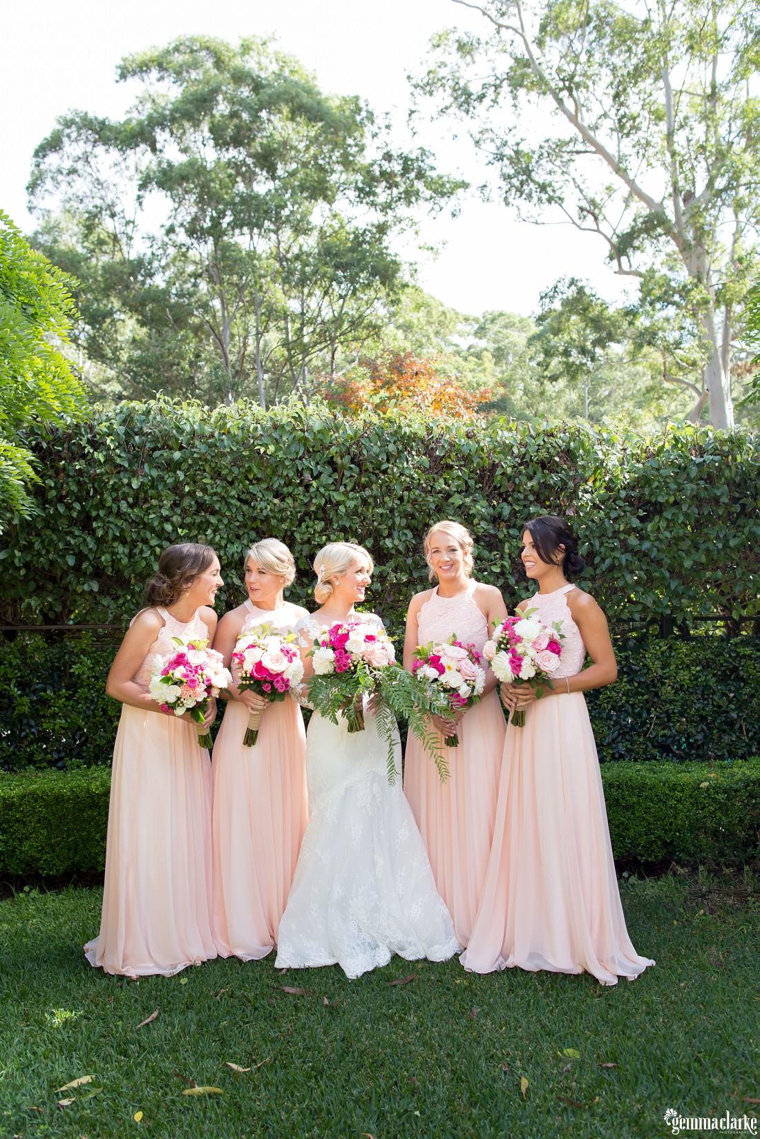 A bride and four bridesmaids holding their bouquets and standing in front of a hedge