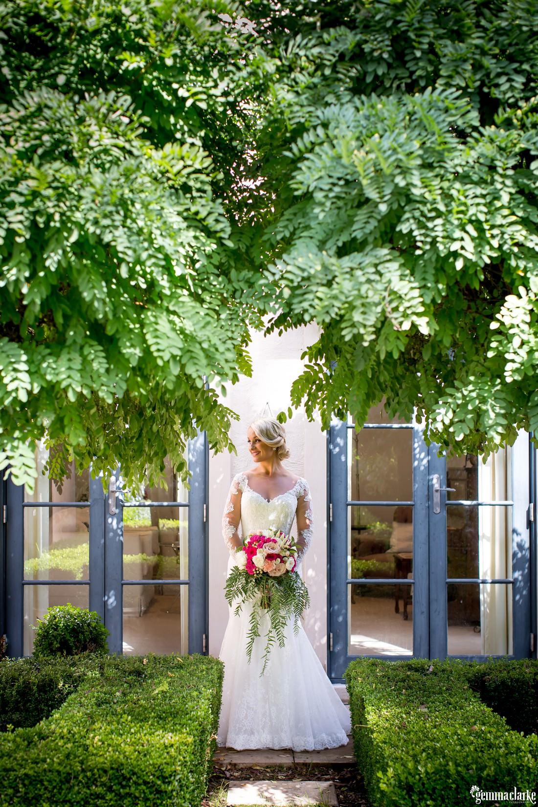 A bride holding a bouquet standing in a garden