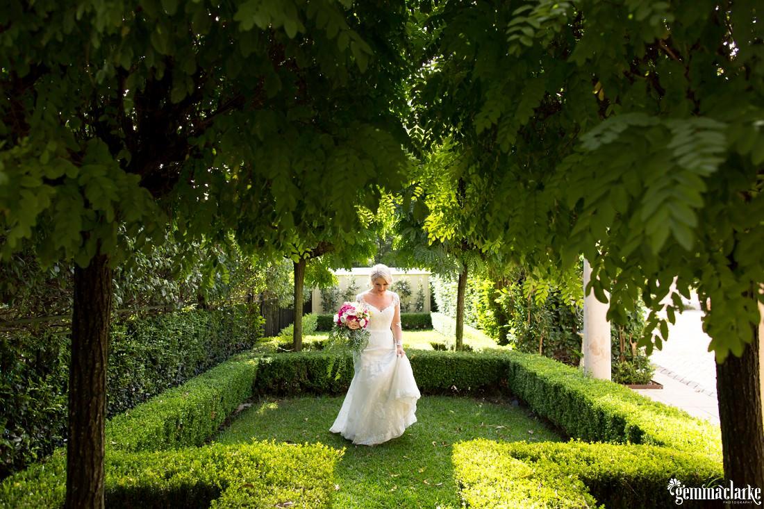 A bride standing in a garden holding her bouquet