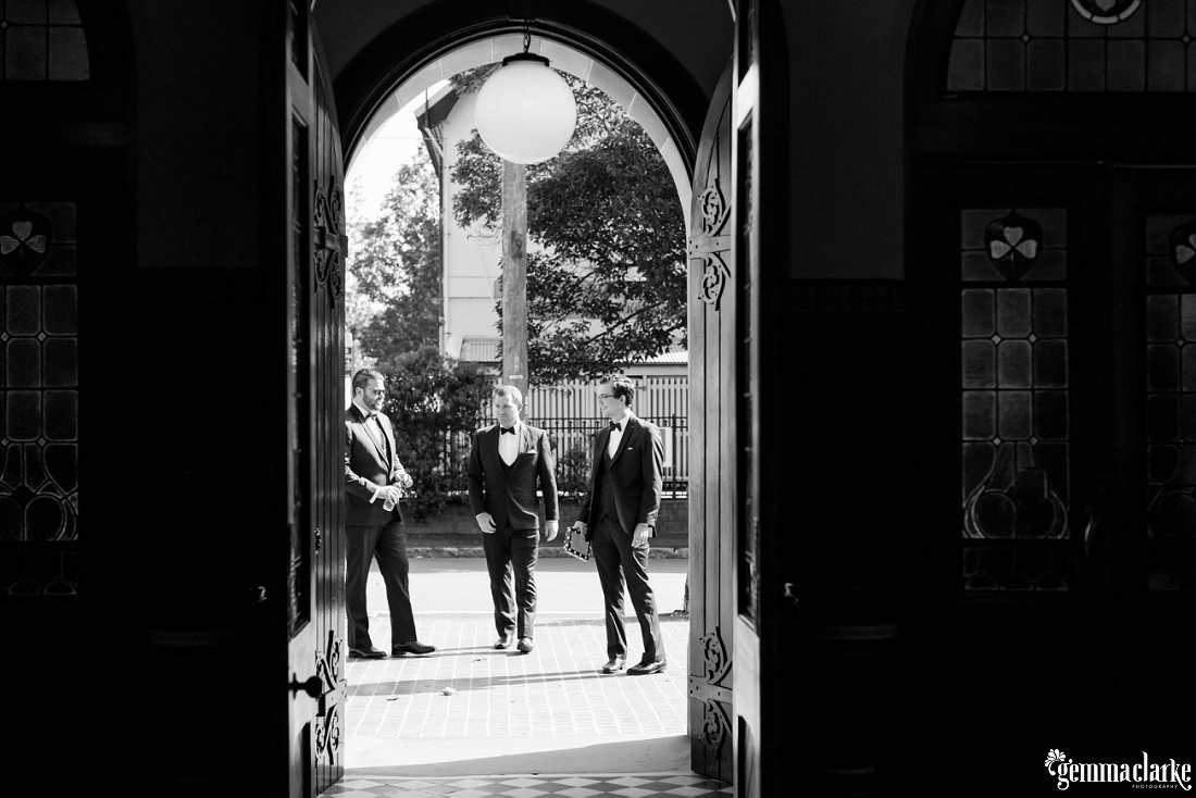 A view out a church door to a groom and his groomsmen