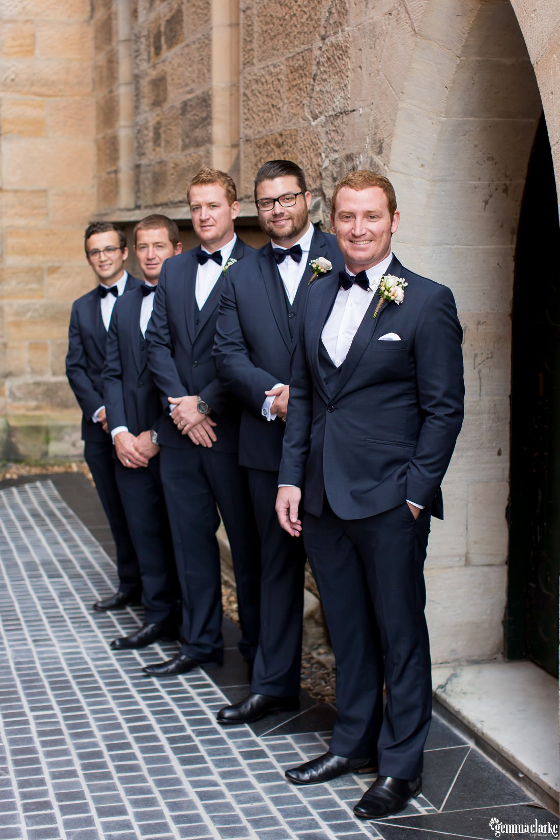 A groom and four groomsmen standing outside a church