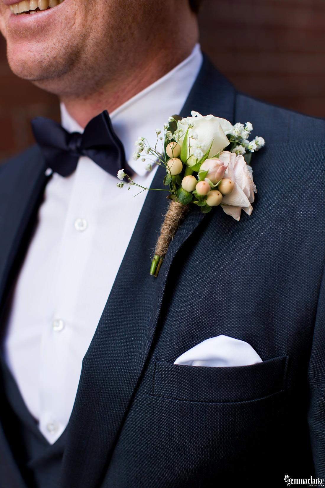 A closeup of a groom's buttonhole flower