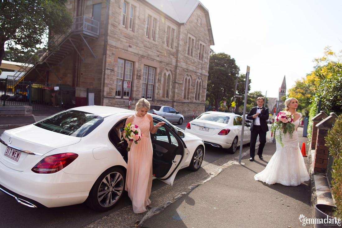 A bride and a bridesmaid emerging from a car about to enter a church