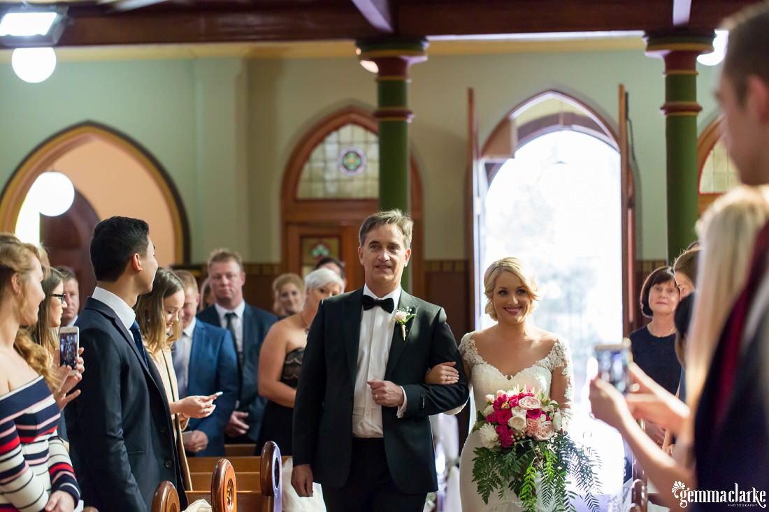 A bride being walking down the aisle by her father