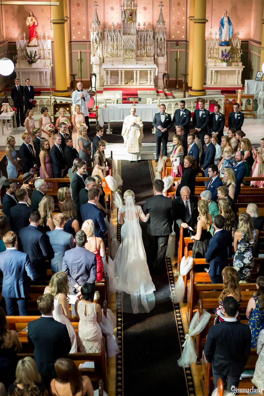 An overhead view of everybody watching a bride being walked down the aisle by her father