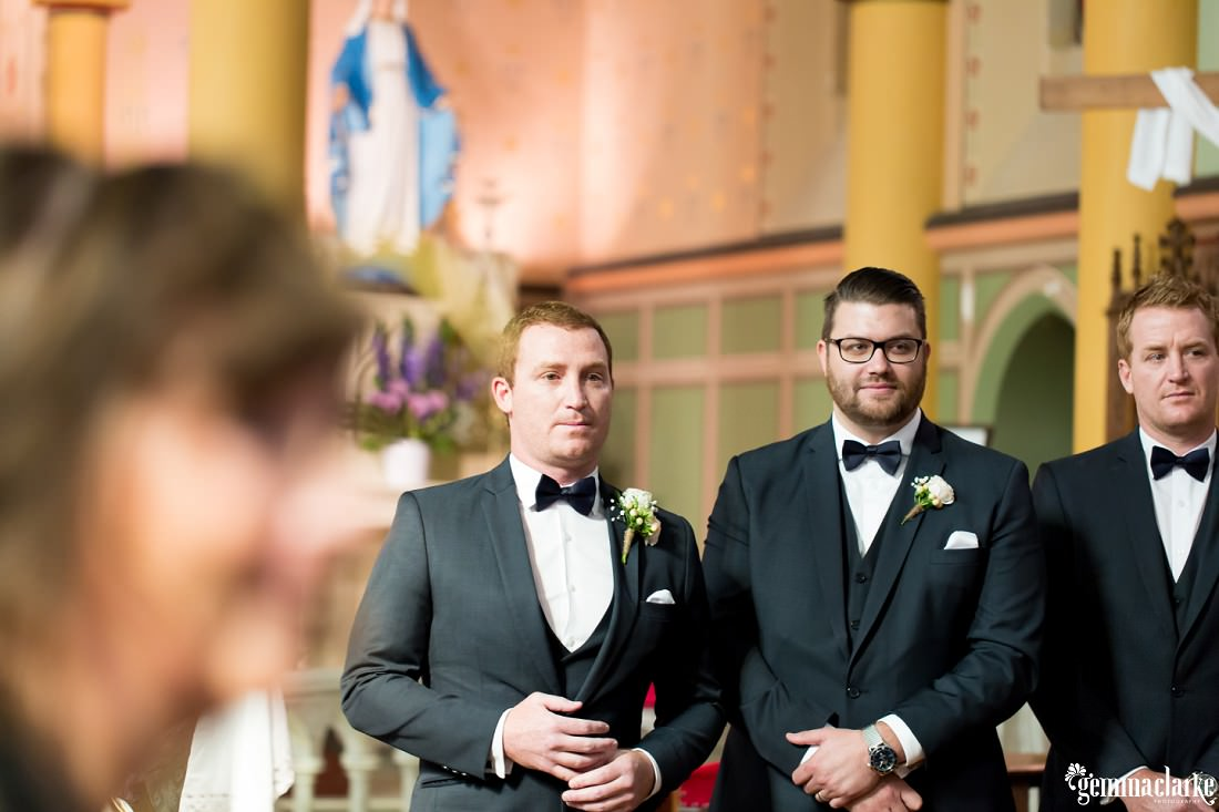 A groom and his groomsmen watching the bride walk down the aisle
