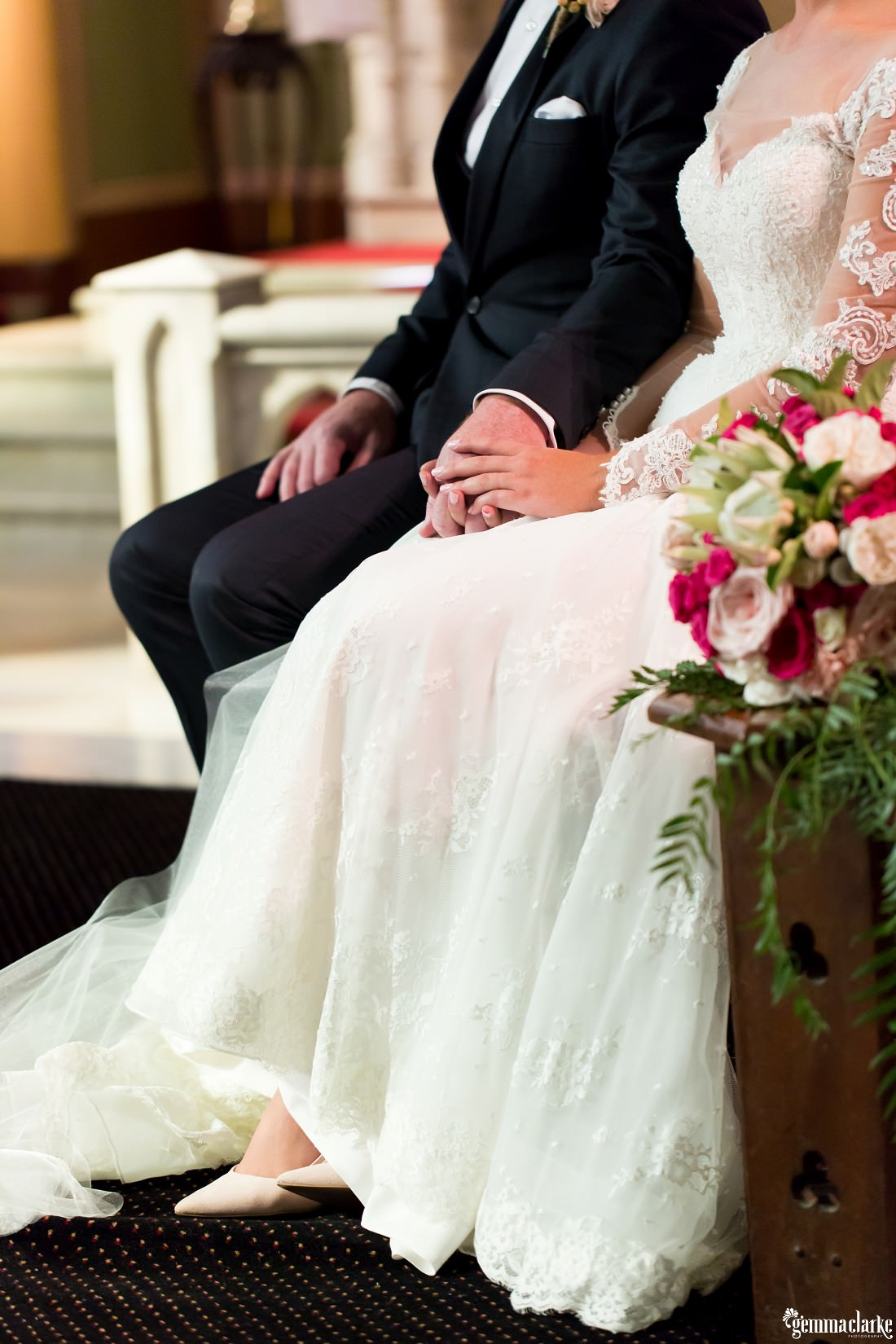 A closeup of a bride and groom holding hands while seated in a church