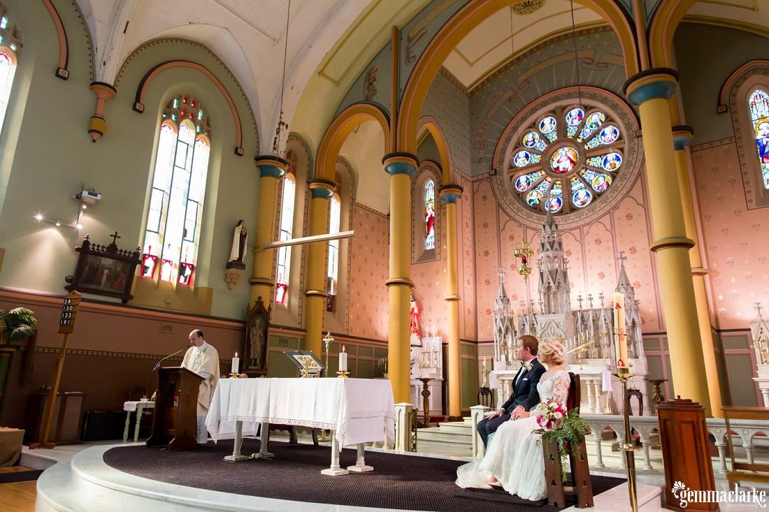 A bride and groom watching as a priest is speaking