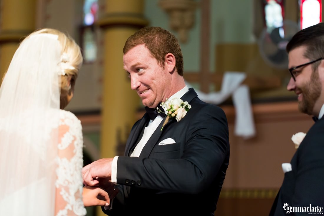 A groom with a funny facial expression as he has trouble putting a ring on his bride's finger