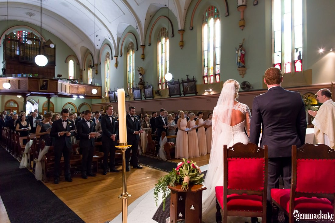 An overall shot of wedding guests in a church with the bride and groom in the foreground