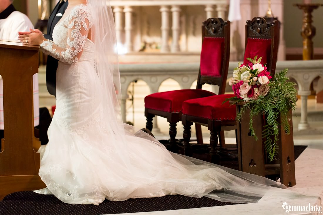 A bride and groom kneeling in front of a pedestal
