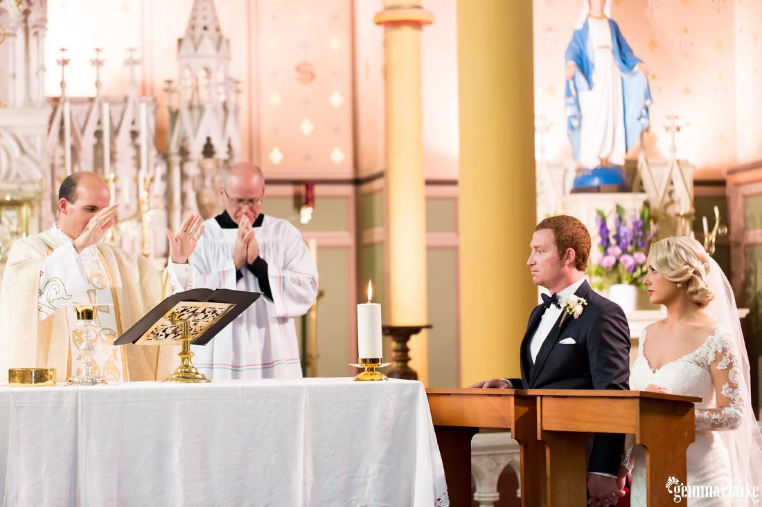 A kneeling bride and groom look on as a priest is speaking