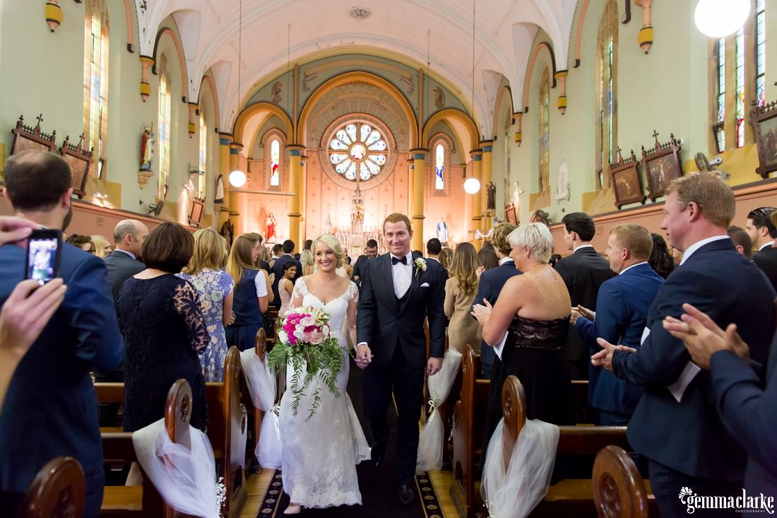 A smiling bride and groom walk down the aisle after they have been married