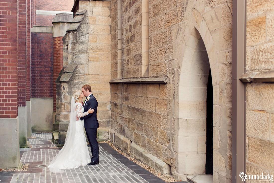 A bride and groom kiss outside a church