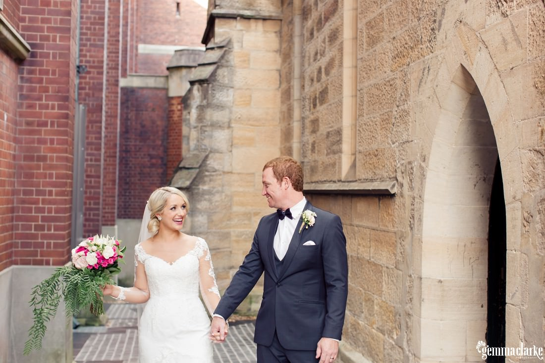 A bride and groom smiling at each other and holding hands outside a church