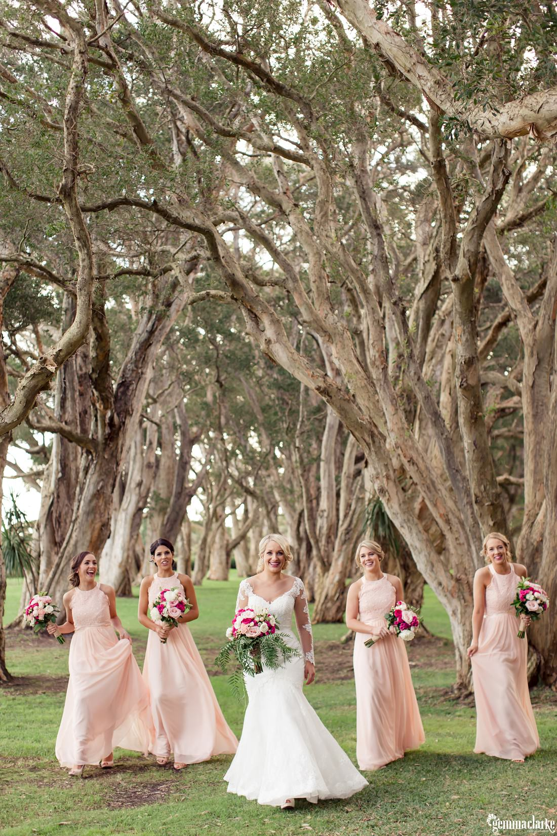 A bride and her bridesmaids walking amongst the trees - Centennial Park Wedding