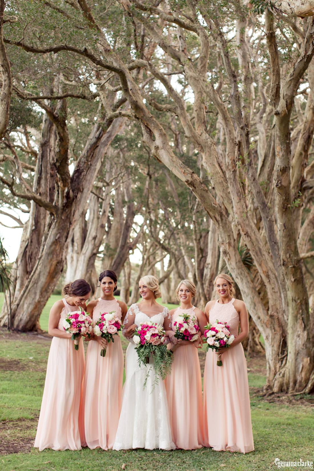 A bride and her bridesmaids standing together in front of some trees - Centennial Park Wedding