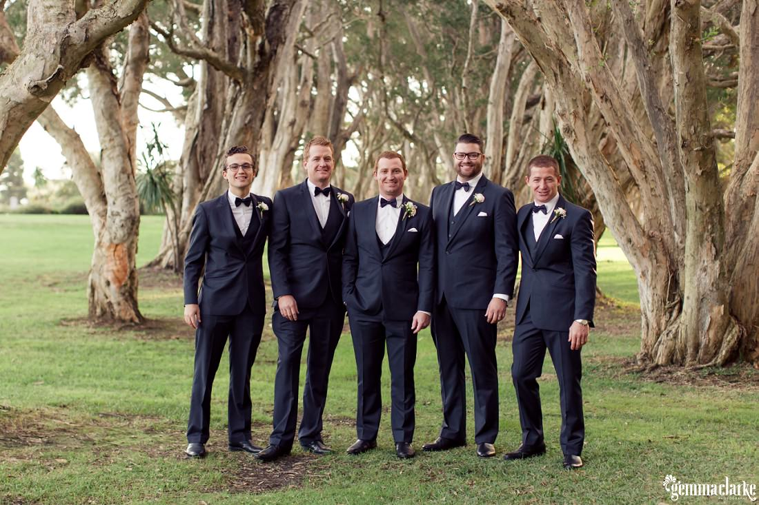 A groom and his groomsmen standing in front of some trees - Centennial Park Wedding