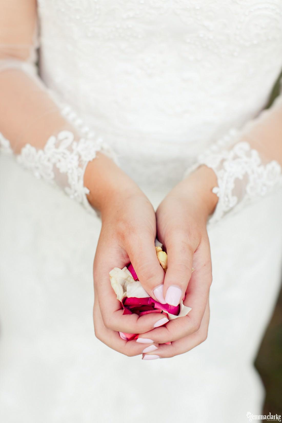 A closeup of a bride's hands holding rose petals