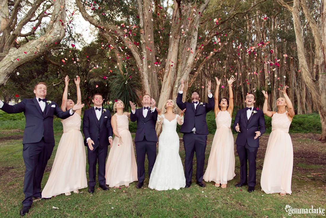 A bridal party throwing rose petals into the air - Centennial Park Wedding