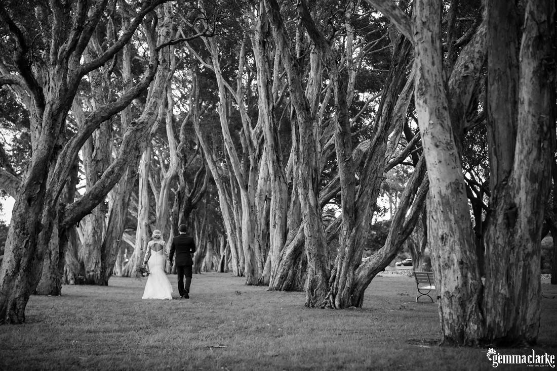 A bride and groom walking through the trees - Centennial Park Wedding