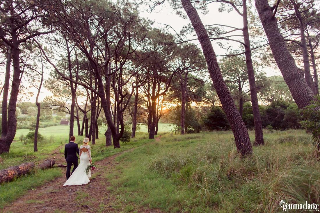 A bride and groom walking through a forest as the sun sets - Centennial Park Wedding