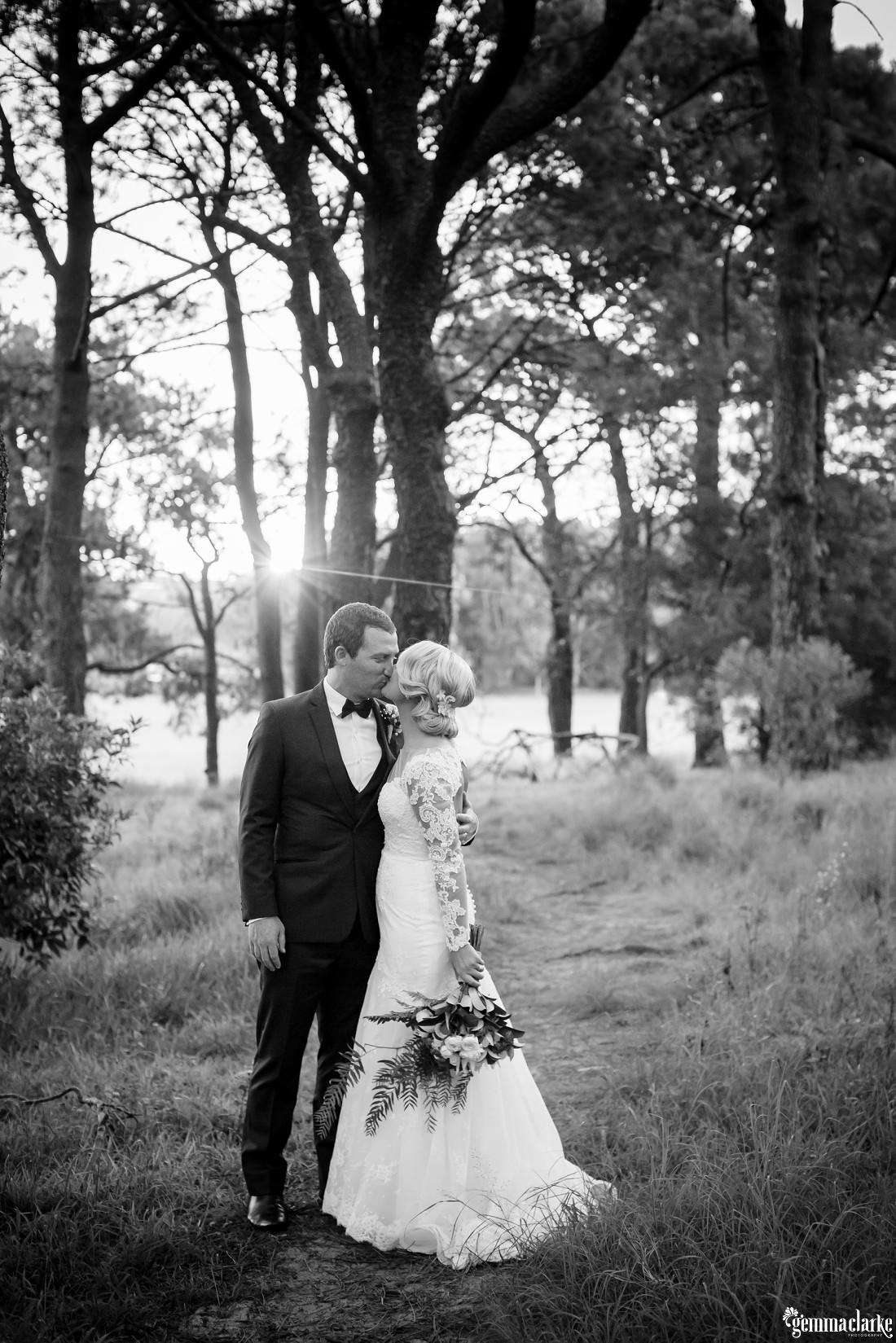A bride and groom kiss as the setting sun shines through the trees behind them - Centennial Park Wedding