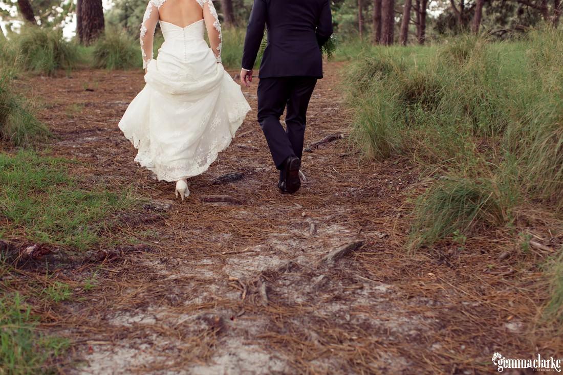 A bride and groom walking through a forest - Centennial Park Wedding