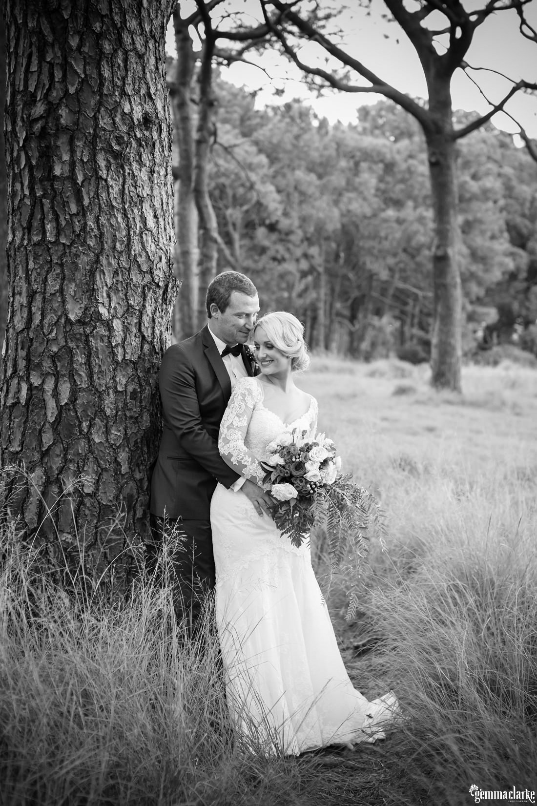 A groom holds his bride and leans against a tree - Centennial Park Wedding