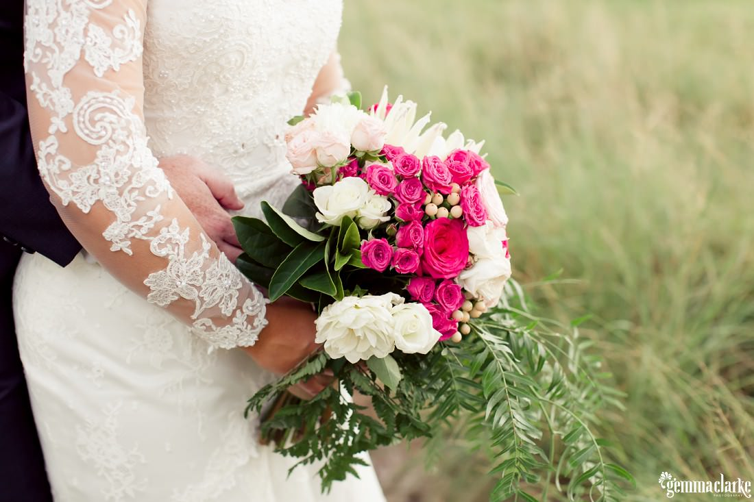 A close up of the detail of a bridal gown and a bouquet of pink and white flowers
