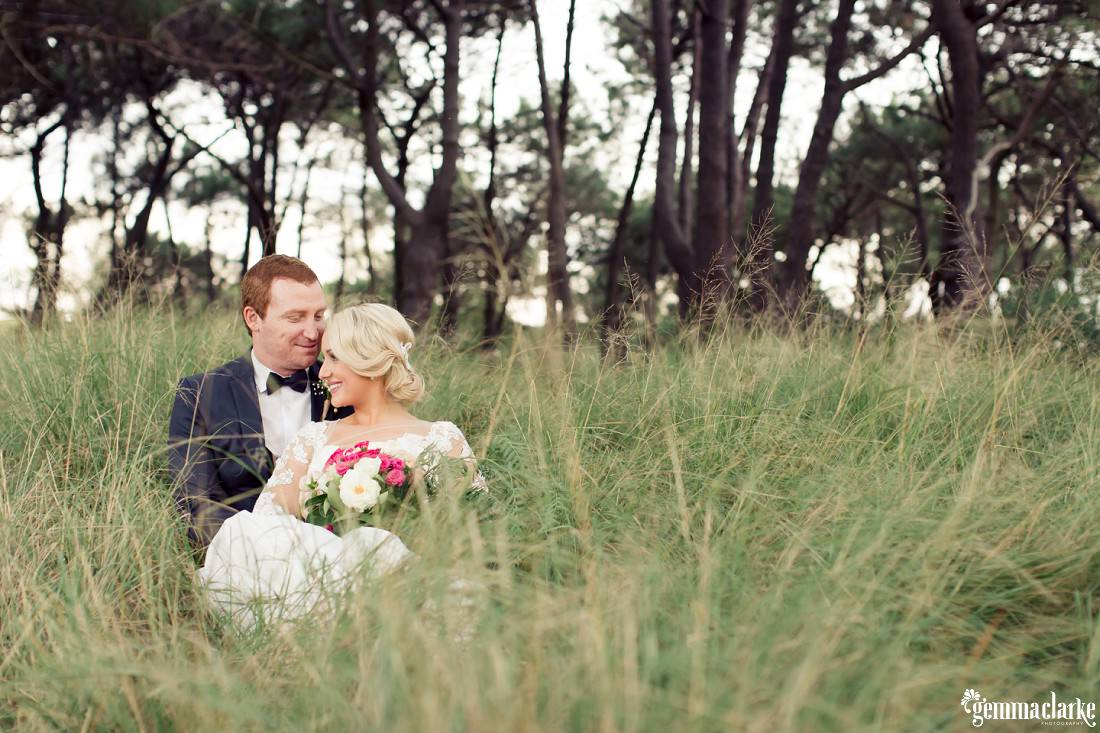 A happy bride and groom lay back in long grass - Centennial Park Wedding