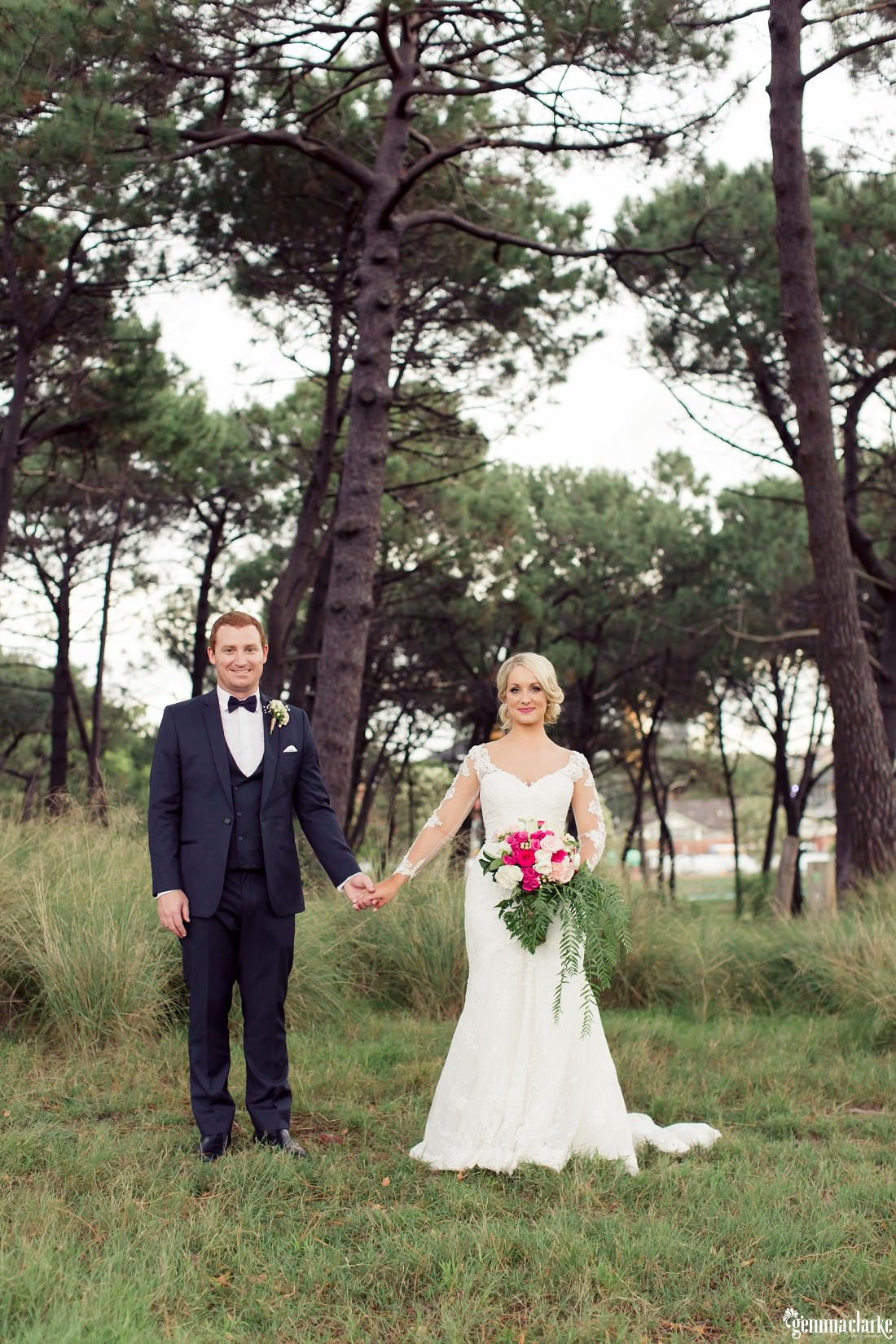A bride and groom smile and hold hands in a forest - Centennial Park Wedding
