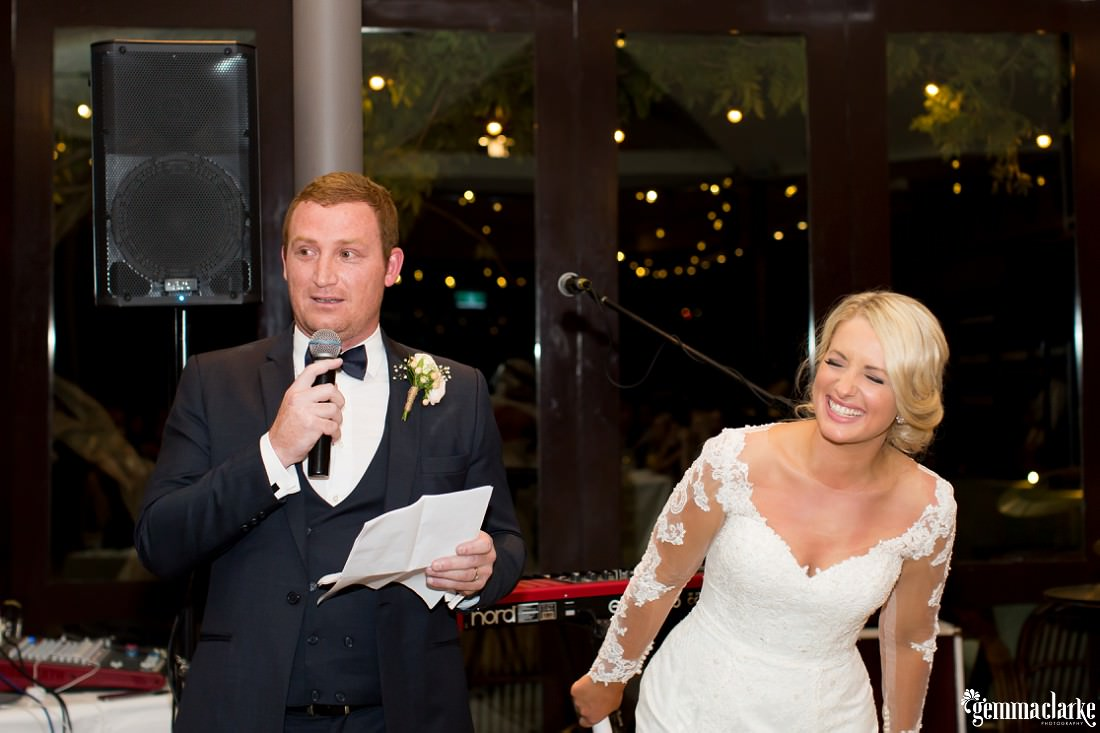 The bride laughs as the groom gives a speech