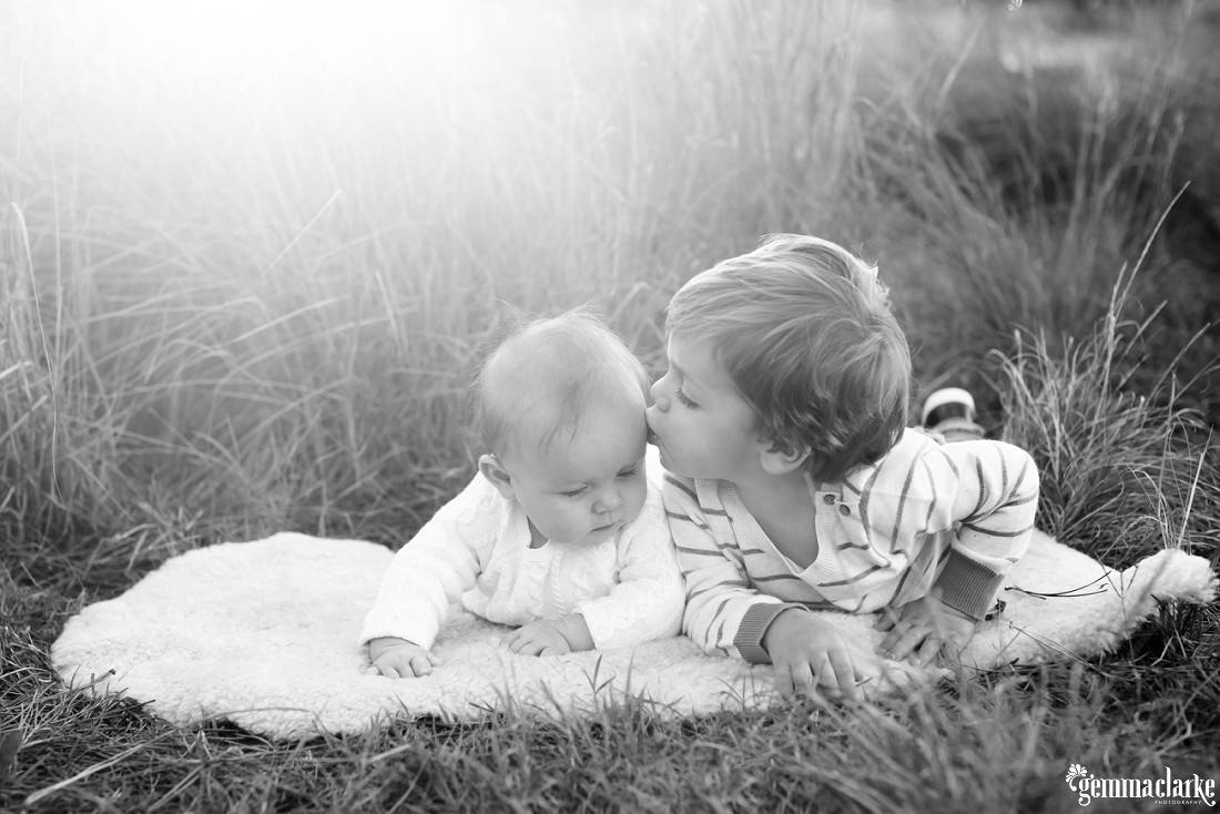 A boy kisses his baby sister while laying on a blanket in long grass