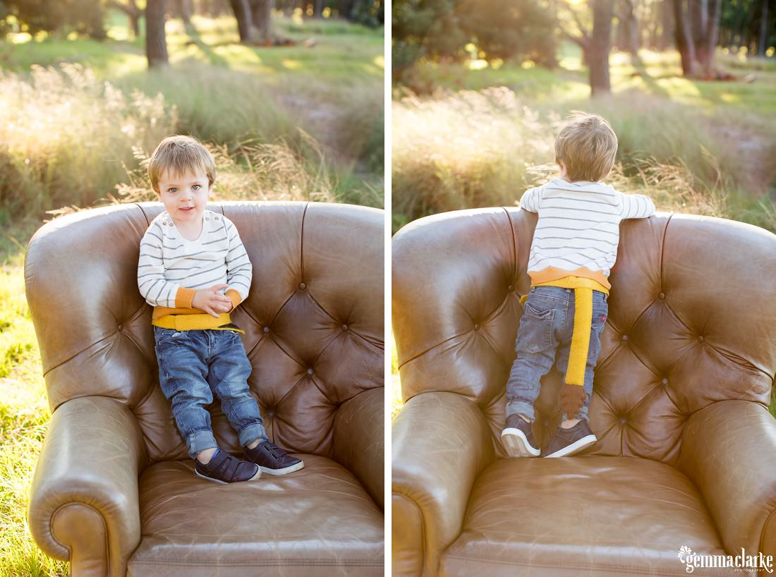 A young boy standing on a leather armchair in a field