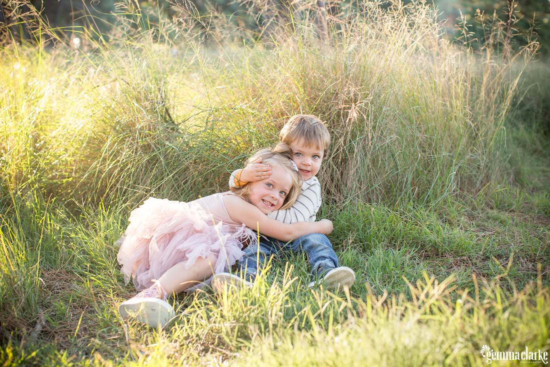 A young brother and sister sit together in long grass