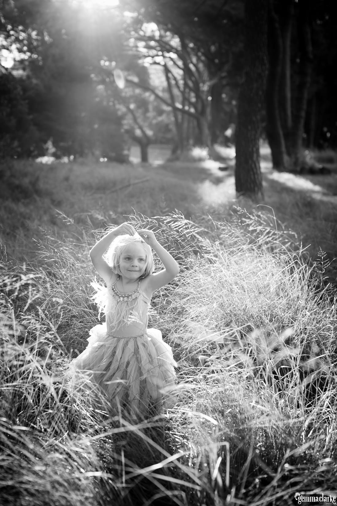 A young girl smiles and strikes a pose in long grass