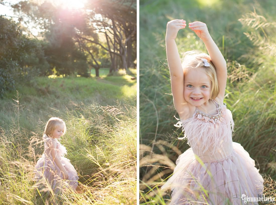 A young girl smiles and poses in long grass with the sun shining through trees in the background