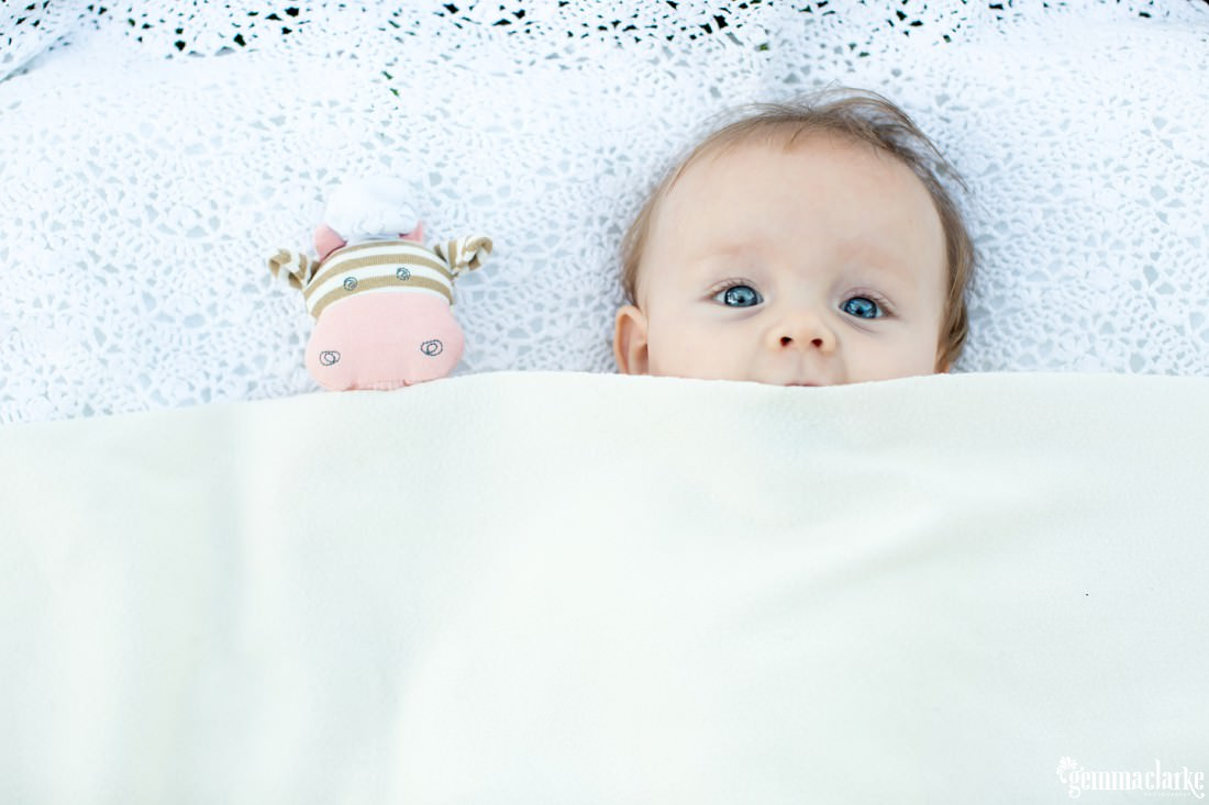 A baby and a toy peeking over the top of a blanket