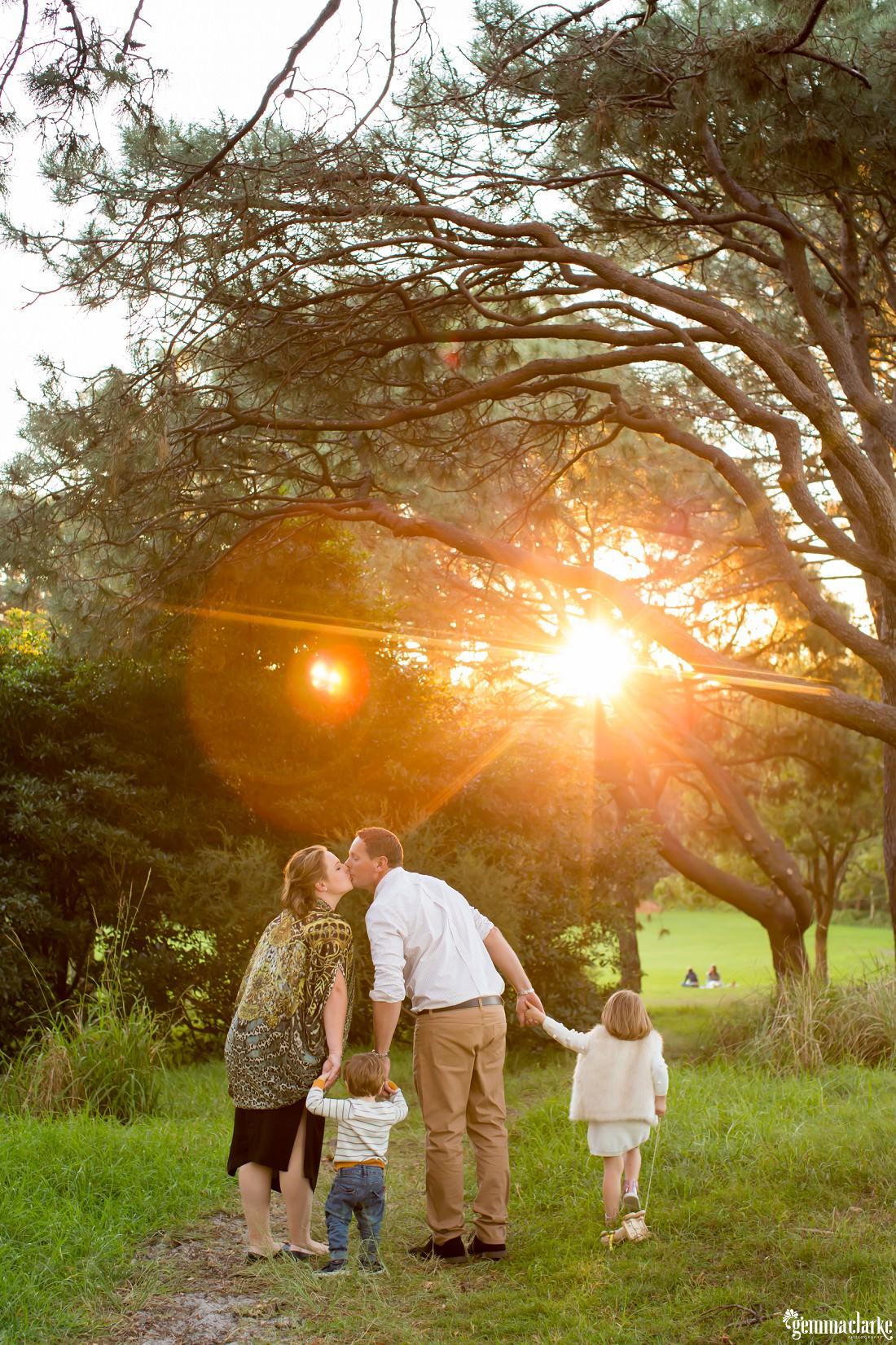 The sun shines through the trees on a kissing couple as they hold hands with their son and daughter